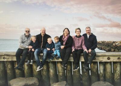 Billede af familie, siddende på bølgebryder i aftensolen på Marina stranden i Bogense