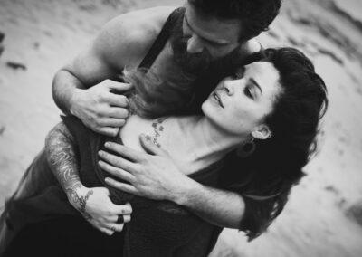 Kærestepar fotograferet på stranden i blæsevejr