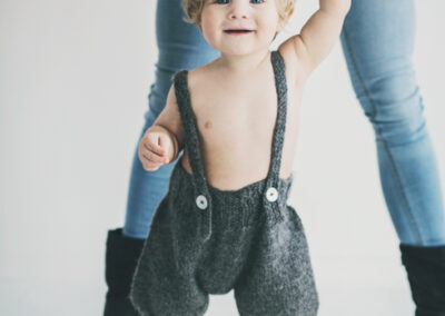 lille dreng i bukser fra Pierrot La Lune, fotograferet med sin mor i hånden og har finde krøller