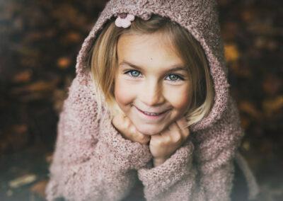pige med flotte øjne og rosa hættetrøje, fotograferet i en skov på Fyn