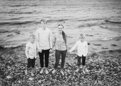 4 søskende der holder i hånd, fotograferet ved vandet