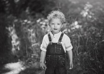 lille dreng i smaekbukser i skoven