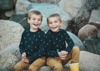 2 broedre griner mens de sidder paa nogen steen
