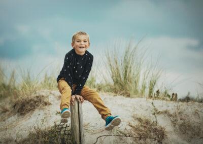 lille dreng leger paa stranden