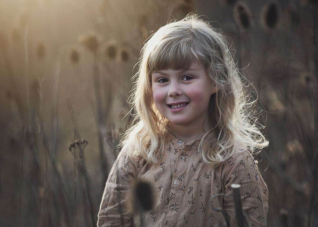 portrat af barn paa stige ø med karteboller i baggrunden