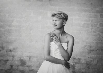 sort hvid billede af pige i hvid kjole foran en murstensvaeg