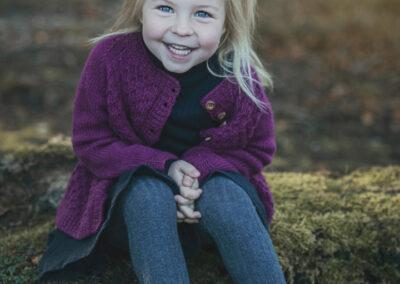 lille pige med blå oejne i lilla striktroeje fotograferet ved langesoe paa nordfyn