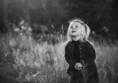 sort-hvid billede af lille pige i hoejt graes