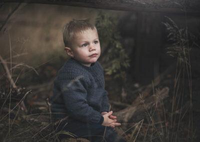 lille dreng sidder og taenker et sted i skoven pa fyn